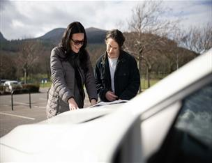 Couple outside a hire vehicle looking at a map.
